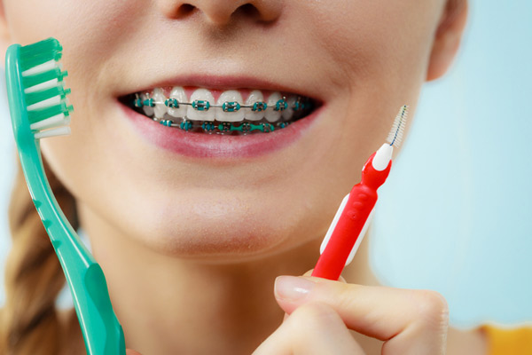 Close up of girl with braces holding interdental and traditional toothbrush